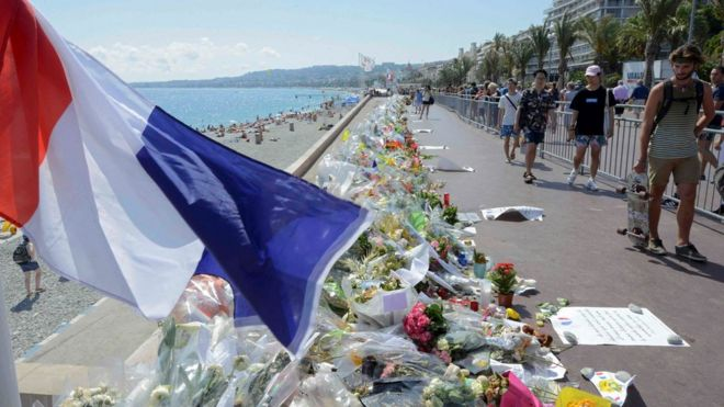 People walk past flowers left in tribute at a makeshift memorial to the victims of the Bastille Day truck attack near the Promenade des Anglais in Nice, France, July 21, 2016.