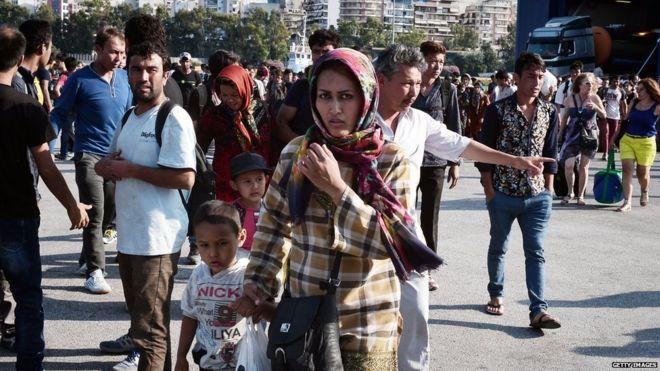 Migranti sbarcano dal traghetto da isola di Lesbo in porto del Pireo nei pressi di Atene. 11 Luglio 2015