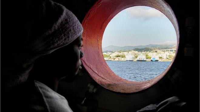 file pic of woman looking out porthole