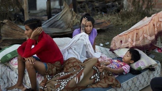 A Ecuadorian family sleeps outside following a powerful earthquake