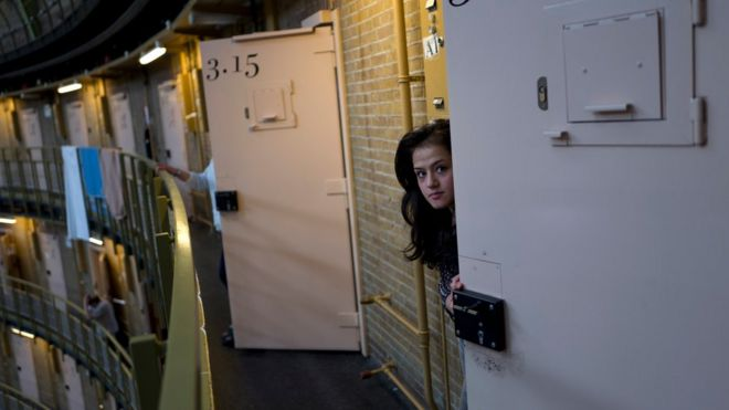 Afghan refugee Shazia Lutfi, 19, peeks through the door of her room at the former prison of De Koepel in Haarlem, Netherlands