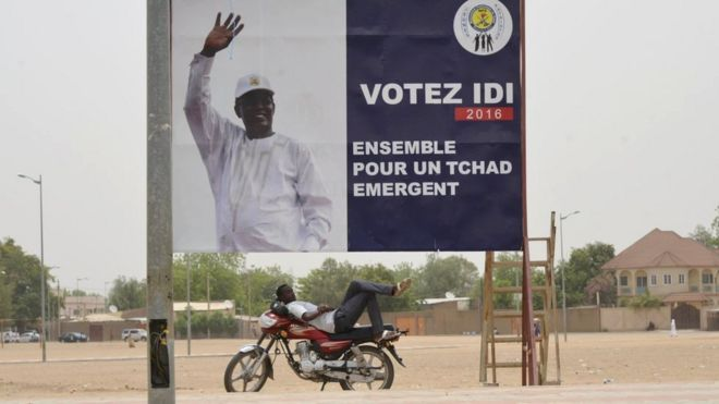 A man resting under a campaign poster of Chad's President Idriss Deby in N'Djamena on 12 April 2016