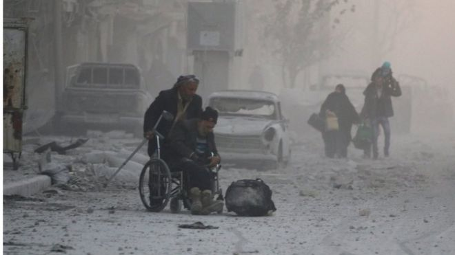A man on a wheelchair flees with others into the remaining rebel-held areas of Aleppo, Syria on 9 December 2016