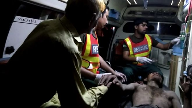 Sadaqat Ali being treated by medical workers