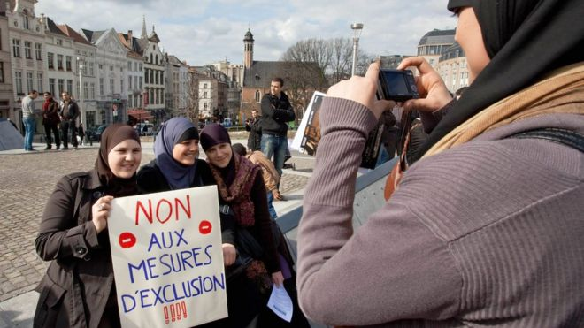Woman takes picture of demonstrators holding placard, reading: 'No to exclusion measures,' during protest on March 27, 2010 in Brussels against prohibition of Muslim headscarf in schools