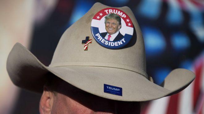Homem com chapéu de cowboy e broches de campanha de Trump