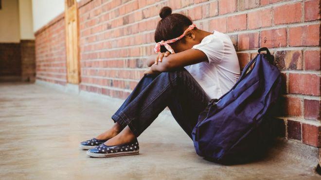 Adolescente sentada ao lado de uma mochila