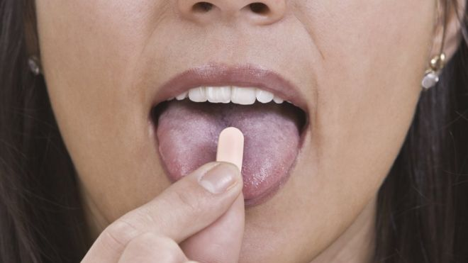 Close up of woman swallowing pill