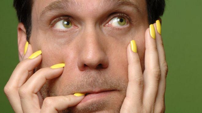 Hombre con manos de mujer en la cara y mordiendo una uña