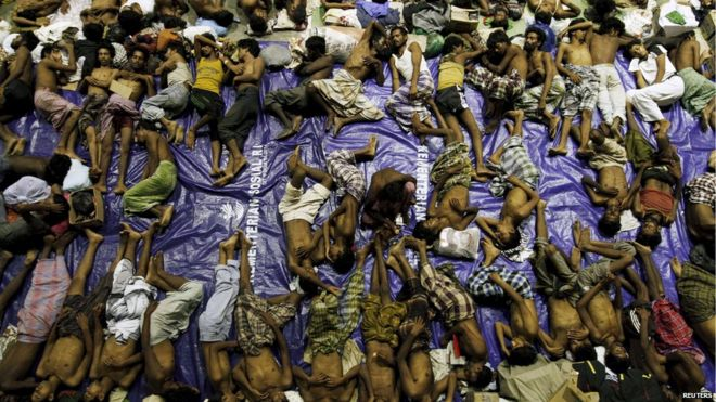 Migrants believed to be Rohingya rest inside a shelter after being rescued from boats at Lhoksukon in Indonesia's Aceh Province on 11 May 2015