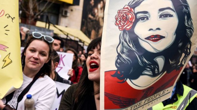 A woman holds a poster by US artist Shepard Ferey and reading 'We the people, defend dignity' as Kosovo feminist supporters take part in a rally for gender equality and against violence towards women to mark the International Women's Day in Pristina on March 8, 2017.