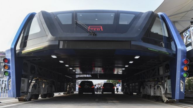 "People look at the Transit Elevated Bus TEB-1 run past vehicles as they conducted a test run in Qinhuangdao, north China""s Hebei Province"
