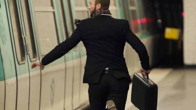 Un hombre corriendo para abordar un tren