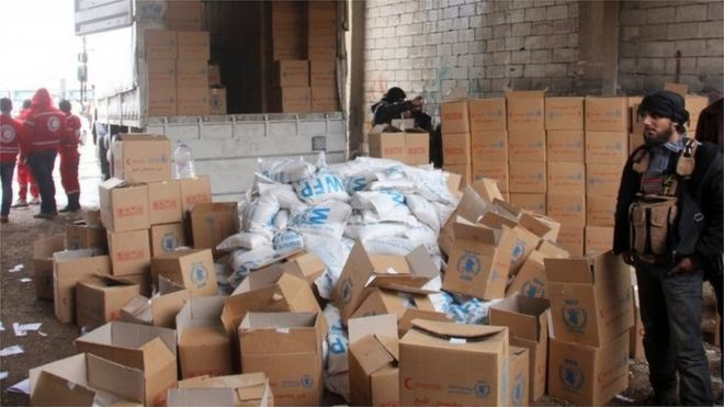 Aid parcels and boxes are offloaded from vehicles in a warehouse in Idlib