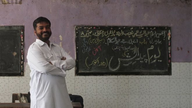 Abdul Wahid Shaikh stands near a blackboard in the school where he teaches