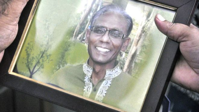 A man holds a portrait of Bangladeshi Professor Siddique, who was hacked to death by unidentified attackers, in Rajshahi on April 23, 2016.