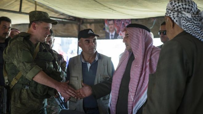 Sheikh Ahmad Mubarak, second from right, shakes hands with a Russian military officer after signing a cease-fire declaration in Maarzaf, about 15 kilometres west of Hama, Syria, Wednesday, March 2, 2016