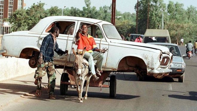 Already busy with thousands of mopeds, the traffic is held up at a crossroads in Ouagadougou, by a donkey cart carrying a car (archive shot)