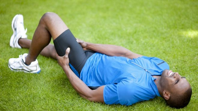 Hombre tomándose la pierna con rostro de dolor