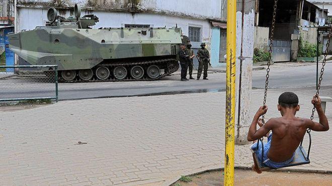 Garoto num balanço observa tanque da Marinha no Rio de Janeiro