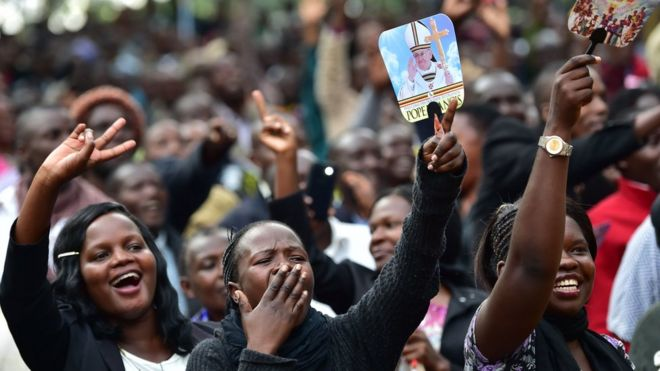 People react as they wait for the arrival of Pope Francis for an open mass in Kampala, Uganda, on Saturday