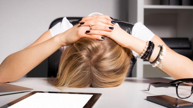 Mujer apoyando cabeza en la mesa