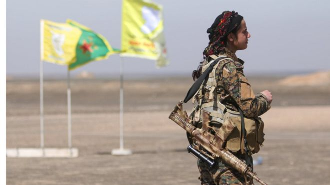 A female Syrian Democratic Forces (SDF) fighter stands with her weapon