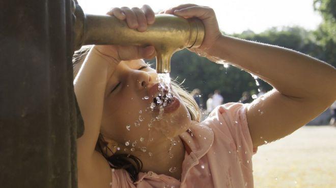 Niña bebe agua de un grifo