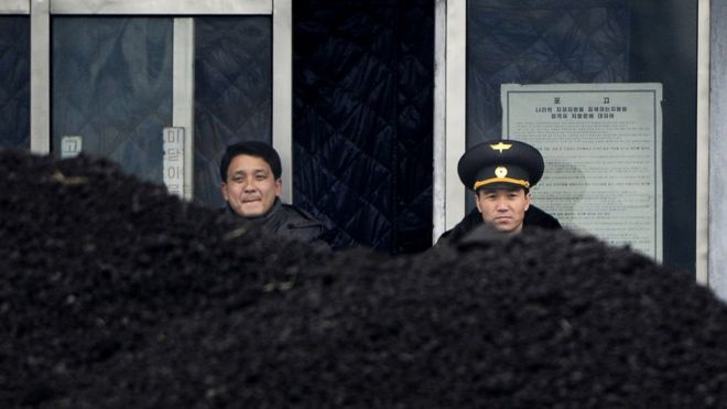 This picture taken on 14 December 2012 from China's northeastern city of Dandong, looking across the border, shows a North Korean military officer (R) and a North Korea man (L) standing behind a pile of coal along the banks of the Yalu River in the northeast of the North Korean border town of Siniuju.