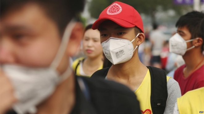 A volunteer (C) wears a mask in a temporary shelter after the explosions in Tianjin on 14 August 2015.