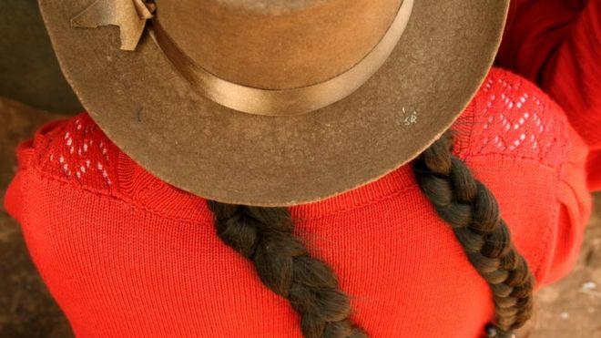 Sombrero y trenzas de una mujer peruana con saco naranja
