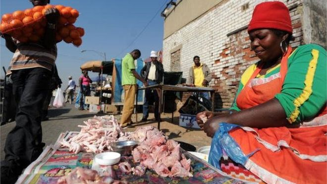 A man carrying oranges walks past a roadside vendor selling chicken strapes at the Alexandra township, near Johannesburg in South Africa.