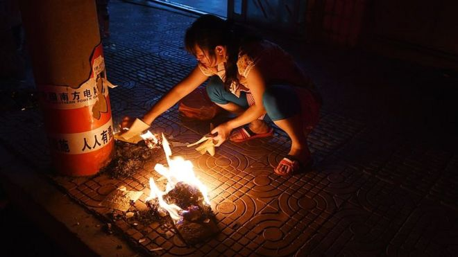This photo taken on August 7, 2014 shows a woman burning paper money to pay respects to deceased ancestors and loved ones during the Ghost Festival, on a sidewalk outside a restaurant in Ludian, in China's southwest Yunnan province.