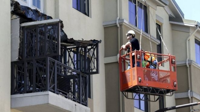 Workmen examine the damage at the scene of a 4th-story apartment building balcony collapse in Berkeley, California June 16, 2015.