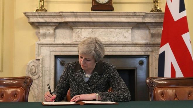 Theresa May oo saxeexaysa warqadii rasmiga ahayd ee Midowga Yurub lagu ogaysiinayey in dalkeedu ka baxay midowga