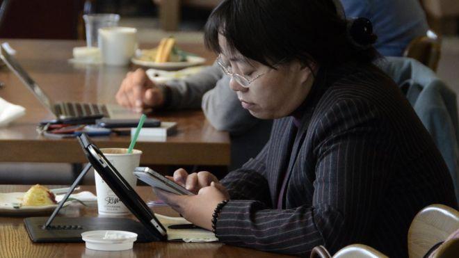 北京某咖啡店内顾客用智能手机和平板电脑上网(资料图片)