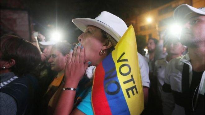 """Una mujer sostiene una bandera que dice """"voté no""""."""