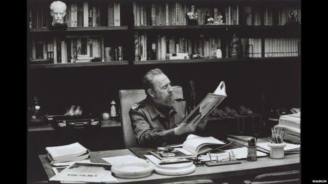 Castro in his office in Havana looking at photographs of the 1959 uprising.; Copyright Burt Glinn / Magnum Photos