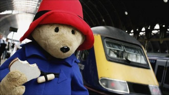 Paddington Bear with marmalade sandwich in hand, about to board a train at Paddington station