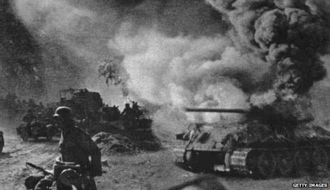 Russian soldiers walk past a burning T-34 tank