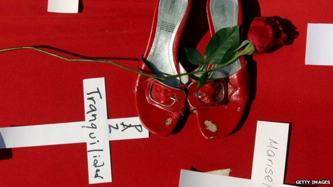 The shoes of a victim are seen next to a flower and a cross during a mass for the commemoration of the first anniversary of a crime in Monterrey, Mexico, in which 52 people died on 25 August, 2012.