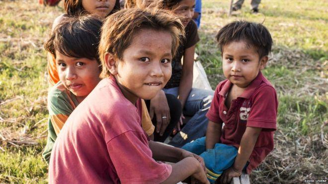 أطفال صغار يلعبون في واحدة من القوارب التي يستخدمها القرويون في موسم الفيضان ، في مانجاليتو