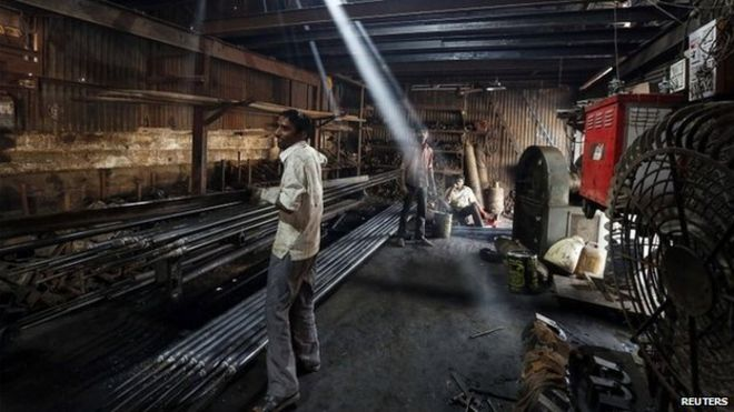 A worker carries an iron pipe inside a metal fabrication workshop in an industrial area of Mumbai February 9, 2015