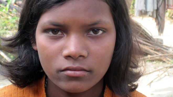 Bijiita Ekka stares fiercely at the camera. She wears an orange shirt and has chin-length hair.