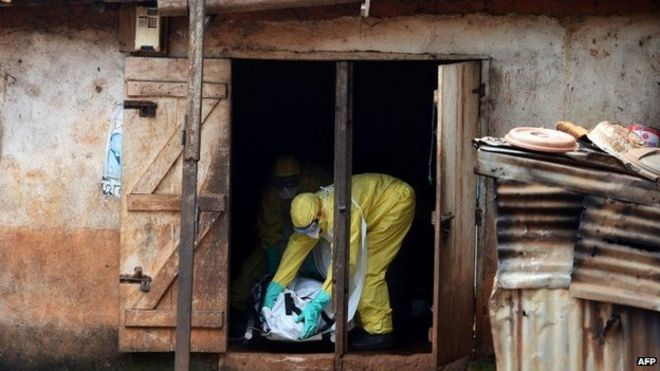 """A file photo taken on November 12, 2014 shows health workers from Sierra Leone""""s Red Cross Society Burial Team 7 preparing to carry a corpse out of a house in Freetown."""