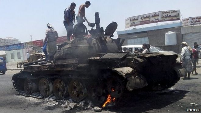 People stand on a tank that was burnt during clashes on a street in Yemen's southern port city of Aden on 29 March 2015.