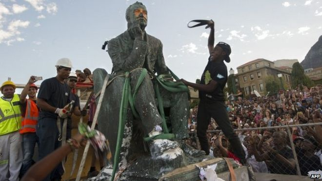 Students attack the defaced statue of British mining magnate and politician, Cecil John Rhodes, as it is removed by a crane from its position at the University of Cape Town on April 9, 2015, in Cape Town