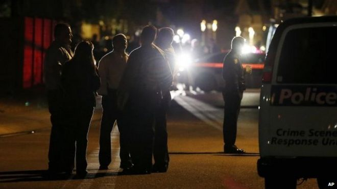 Members of the Phoenix Police Department stand out in front of a home where authorities say five people were killed inside after a shooting
