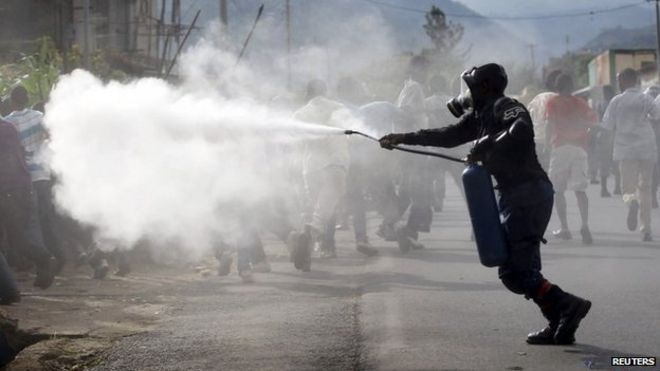 A riot police officer sprays teargas on residents participating in street protests in Burundi