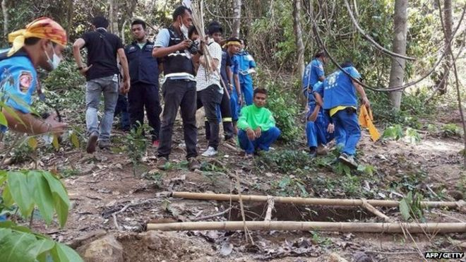 Rescue workers and forensic officials inspect the site of a mass grave uncovered at an abandoned jungle camp in the Sadao district of Thailand's southern Songkhla province bordering Malaysia on 1 May 2015.